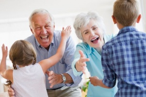 Grandparents holding out their arms to hug grandchildren